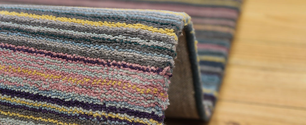 Detail view of a cut pile woollen rug showing cut strands