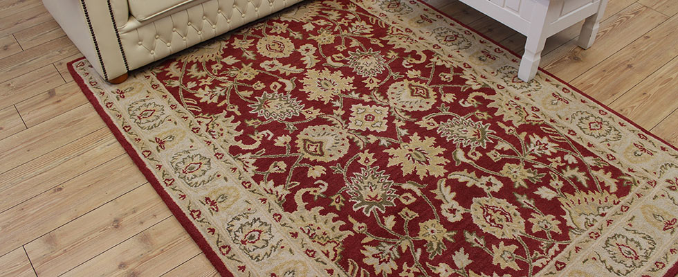 Large woollen rug with classic pattern in front of a cream sofa