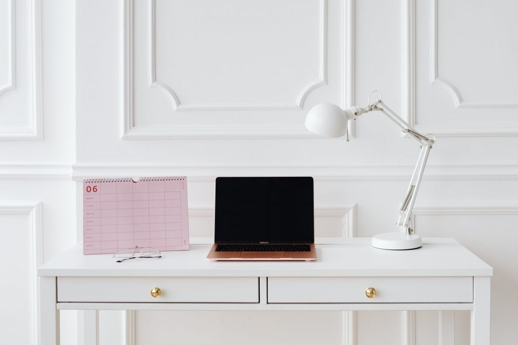 minimalist home office design with macbook and calendar on white desk