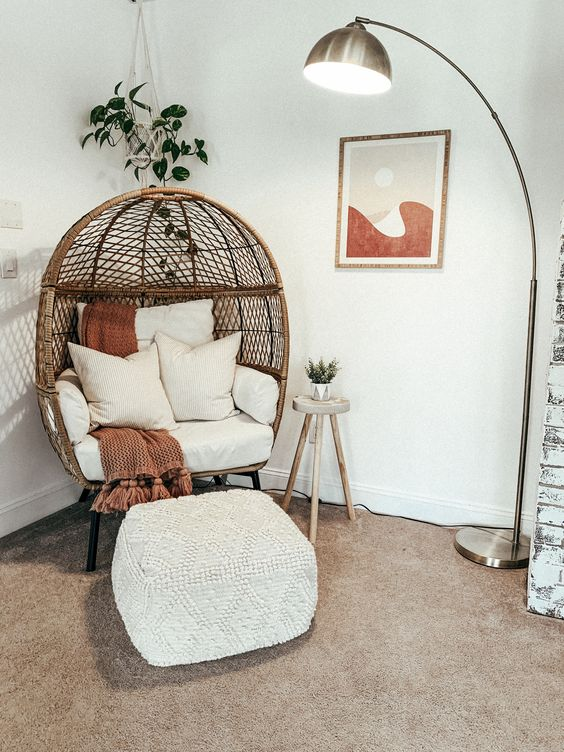 reading nook with comfy wicker chair and footstool located in the corner of a room