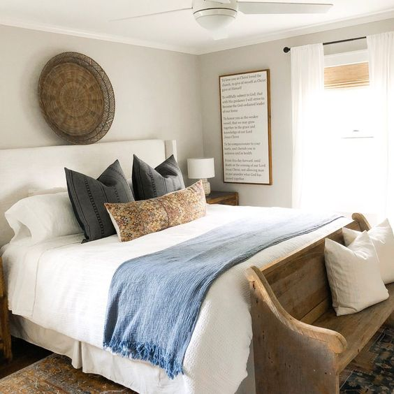 double bed with white duvets, charcoal coloured cushions and blue throw