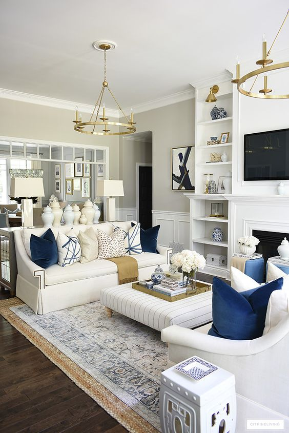 Luxe living room design with large living room Moroccan rug and white sofas used.
