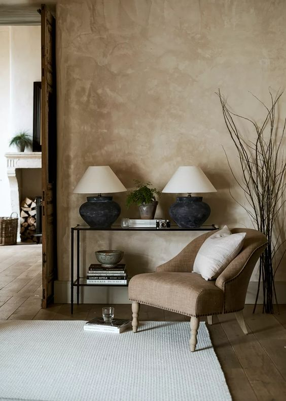 living room with white rug, taupe chair used within the space and lime washed walls